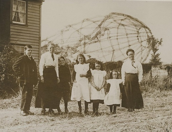 mother and children in front on a house with zeppelin remains in the background